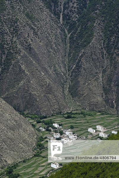 Blick von oben auf die tibetische Architektur eines kleinen Dorfes  Häuser inmitten eines steilen Canyons mit Feldterrassen zum Anbau  Xiangcheng  Chaktreng  Kham  Sichuan  China  Asien