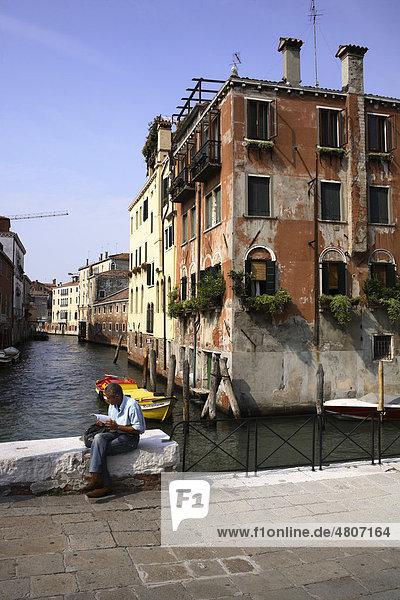 Mann beim Zeitunglesen an einem Kanal  Venedig  Italien  Europa