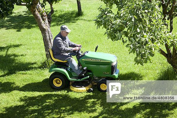 Älterer Mann mäht den Rasen auf einem Aufsitzrasenmäher von John Deere in Bengel  Rheinland-Pfalz  Deutschland  Europa