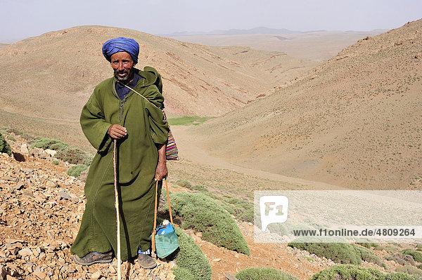 Ziegenhirte  älterer Mann mit Djellabah  Turban und Wasserflasche in den Bergen des Hohen Atlas  Marokko  Afrika