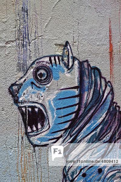 Graffiti eines Fabelwesens mit aufgerissenem Maul und spitzen Zähnen an einer Hauswand