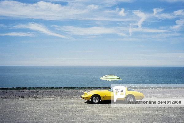 Gelber Chevrolet Corvette mit Sonnenschirm parkt am Meeresufer  Westkapelle  Walcheren  Provinz Zeeland  Niederlande  Benelux  Europa