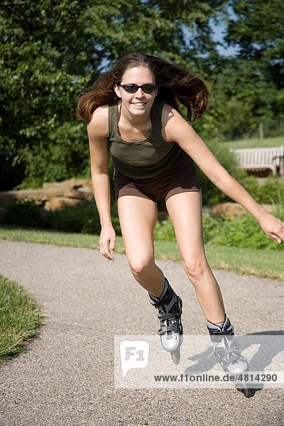 Young woman in early 20s roller blading in park