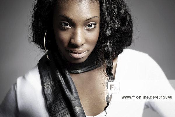 Portrait einer jungen dunkelhäutigen Frau mit Schal über Schulter  direkter Blick