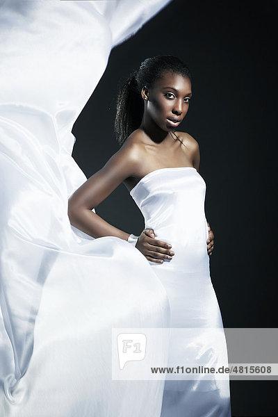 Junge dunkelhäutige Frau in einem weißen Seidenkleid mit wehender Schleppe