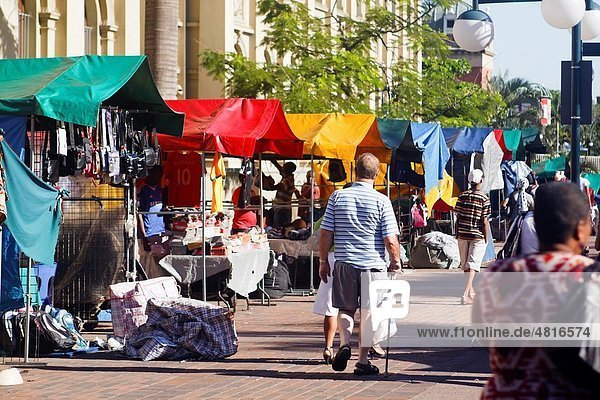 Hawkers setting up colourful street-side stalls along a busy city thoroughfare in central Durban  South Africa
