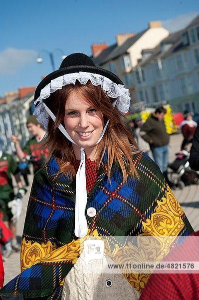 A young woman dressed in traditional welsh costume on St Davids Day Wales UK