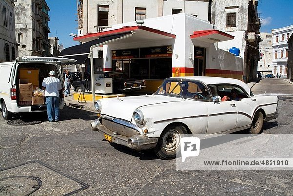 Classic American car passing by a gas station in Havana  Cuba