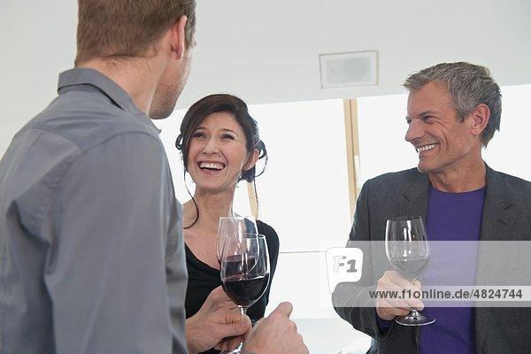 Männer und Frauen  die Wein trinken  lächelnd