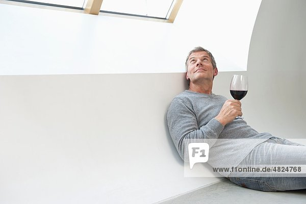 Mature man with wine glass at home