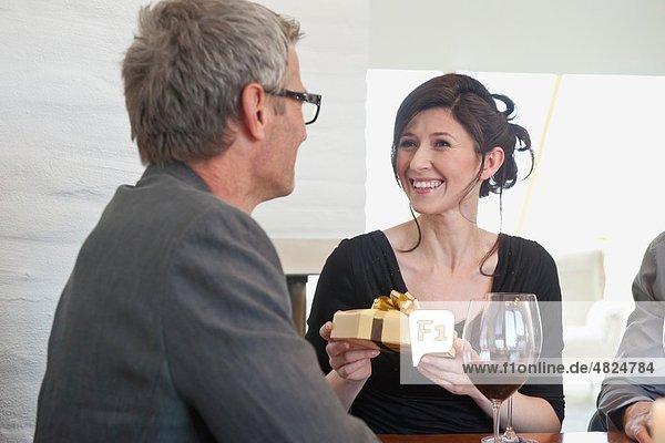 Frau schenkt dem älteren Mann eine Geschenkbox