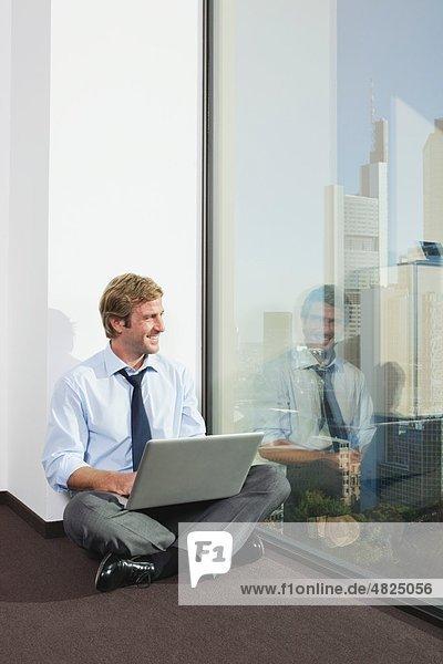 Deutschland  Frankfurt  Geschäftsmann mit Laptop im Büro