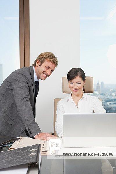 Deutschland  Frankfurt  Geschäftsleute mit Laptop im Büro