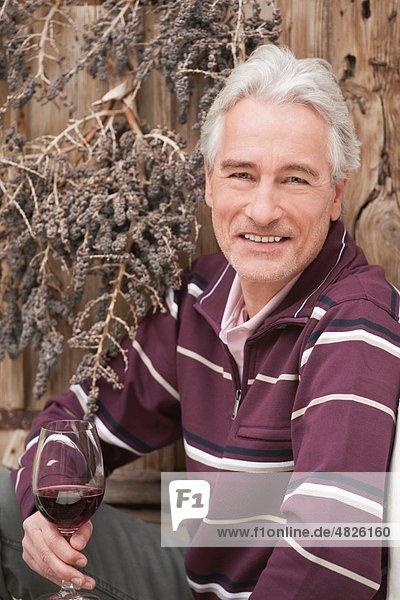 Italien  Südtirol  reifer Mann mit Weinglas  lächelnd  Portrait