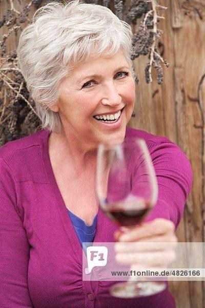 Italien  Südtirol  Reife Frau mit Weinglas  lächelnd  Portrait
