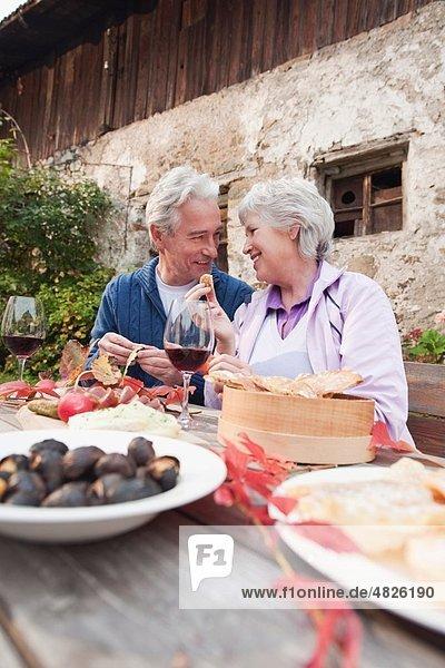 Italien  Südtirol  Reife Paare beim Snacken auf der Berghütte