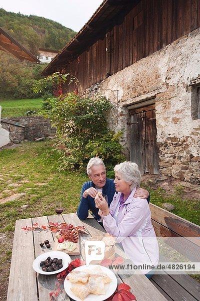 Italien  Südtirol  reifes Paar beim Reden und Snacken auf der Berghütte