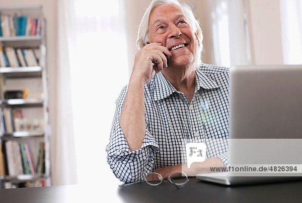 Senior Mann am Telefon mit Laptop  lächelnd