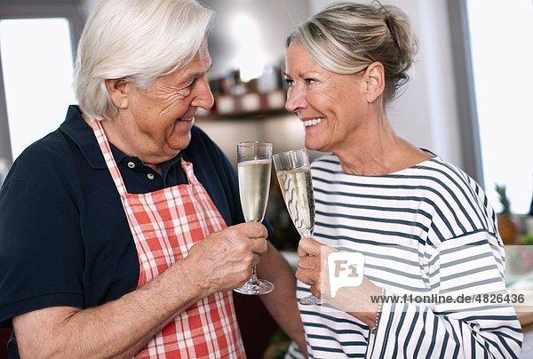 Deutschland  Wakendorf  Seniorenpaar mit Getränk  lächelnd