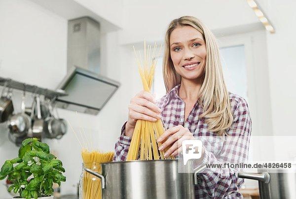Frau kocht Spaghetti  Portrait  lächelnd