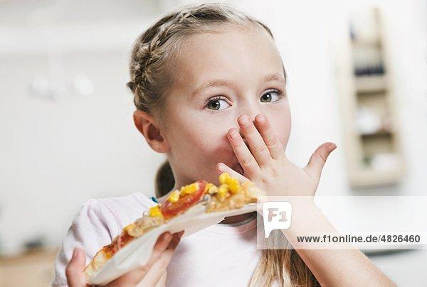Ein Mädchen isst eine Scheibe Pizza.