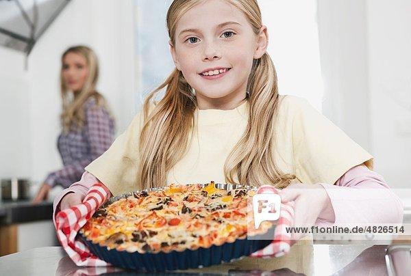 Mädchen mit Pizza und Mutter im Hintergrund