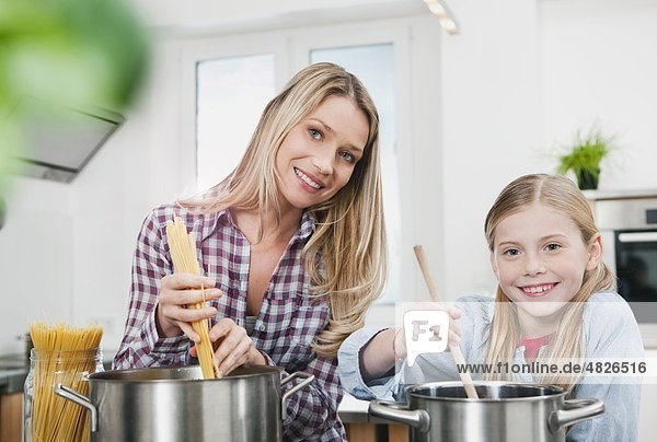 Germany    Mother and daughter cooking spaghetti