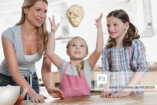 Deutschland    Mutter und Kinder bei der Teigbereitung