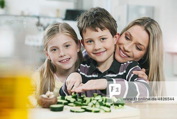 Deutschland    Mutter und Kinder schneiden Gemüse in der Küche