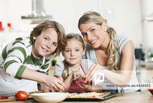 Deutschland    Mutter und Kinder machen Pizza in der Küche