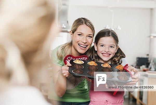 Deutschland    Mutter und Tochter halten Törtchen im Backblech  lächelnd