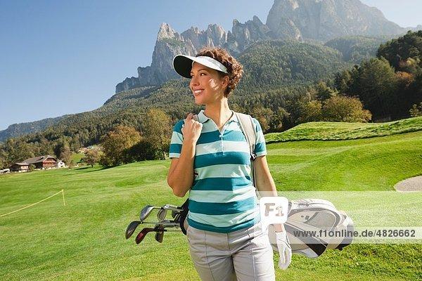 Italien  Kastelruth  Mittlere erwachsene Frau mit Golftasche auf dem Golfplatz