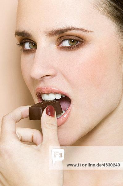 Junge Frau beißt Schokolade