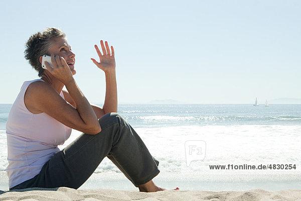 Seniorin mit Handy am Strand