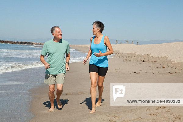 Seniorenpaar beim Joggen am Strand