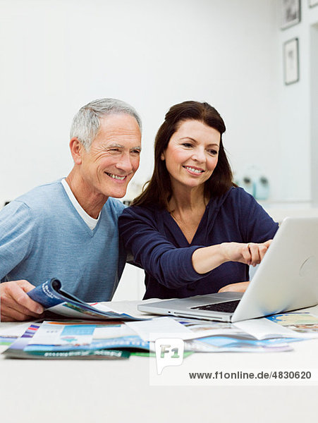 Reife Paare  die ihren Urlaub mit dem Laptop buchen.