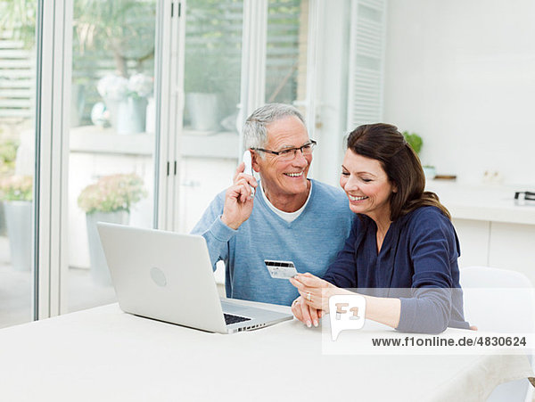 Erwachsenes Paar mit Laptop,  Mann am Telefon