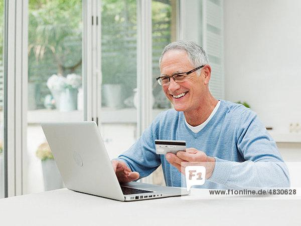 Senior Mann mit Laptop und Kreditkarte