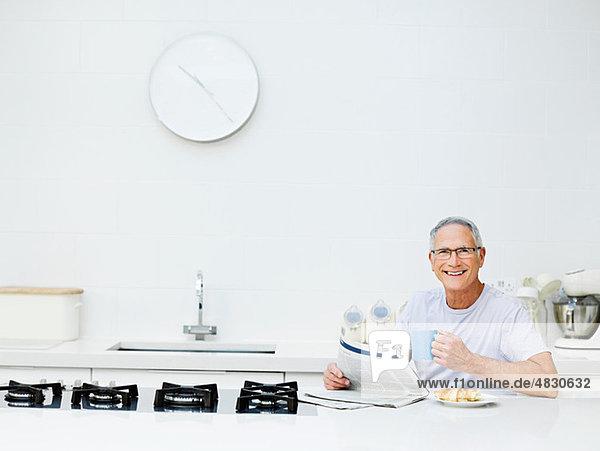 Senior Mann beim Frühstücken,  Zeitung lesen