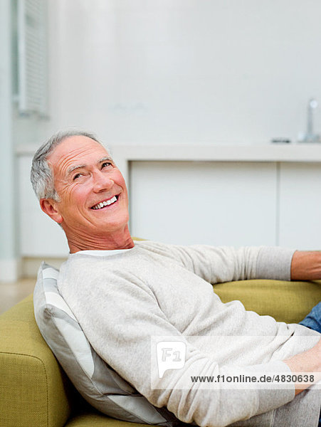 Senior auf dem Sofa sitzend