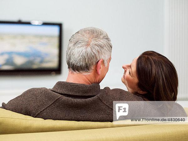 Ein reifes Paar sitzt auf dem Sofa und schaut fern.