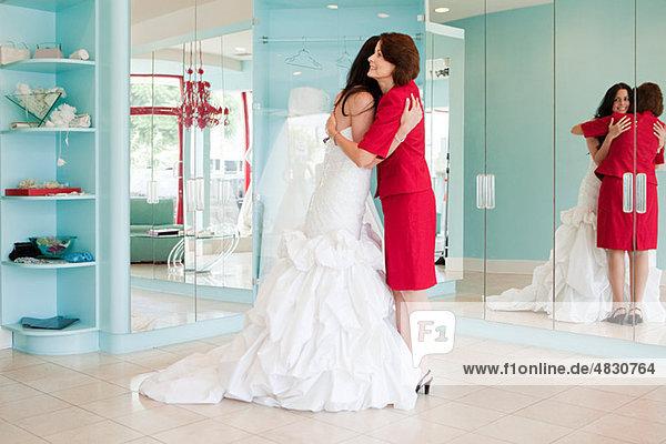 Tochter versuchen auf Hochzeitskleid  umarmen  Mutter