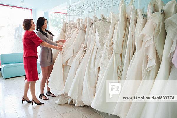 Mutter und Tochter beim Betrachten von Hochzeitskleidern Mutter und Tochter beim Betrachten von Hochzeitskleidern