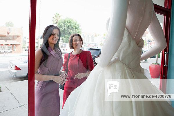 Mutter und Tochter beim Anblick des Hochzeitskleides im Schaufenster Mutter und Tochter beim Anblick des Hochzeitskleides im Schaufenster