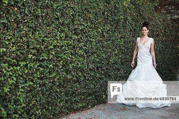 Junge Frau im Brautkleid  an der Hecke stehend