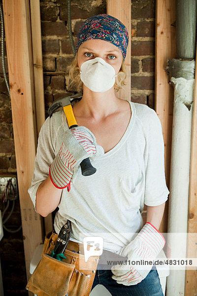 Frau trägt Handschuhe mit hammer