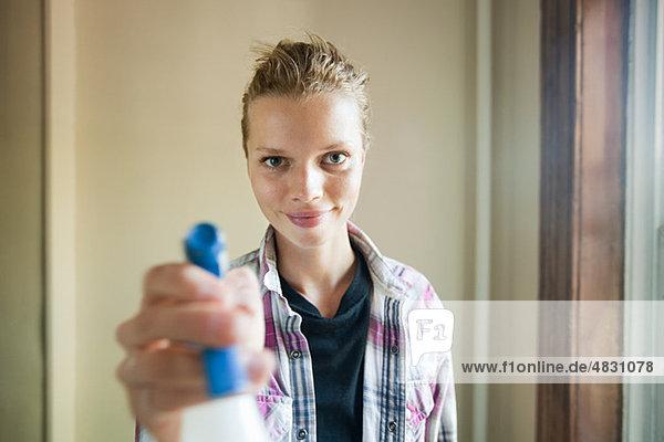 Frau mit Reinigungsflüssigkeitssprüher