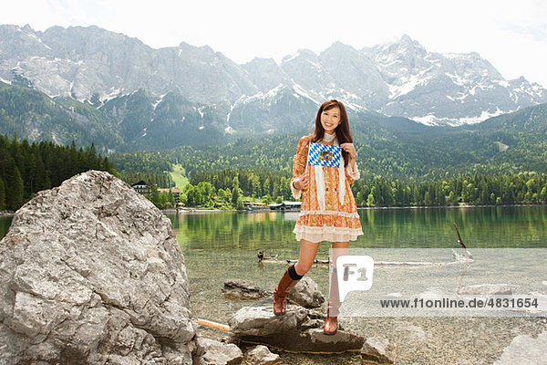 Woman with Bavarian flag  Lake Eibsee and Mount Zugspitze in background  Bavaria  Germany