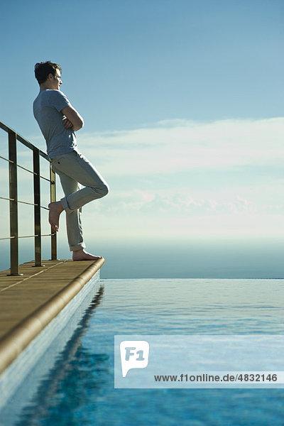 Mann lehnt am Geländer neben dem Unendlichkeitsbecken  Blick auf die Aussicht