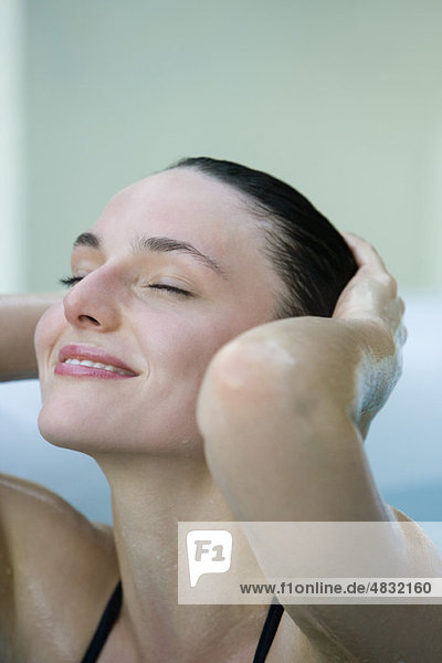 Woman smoothing back wet hair, eyes closed PAA595000039